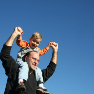Man holds small child on his shoulders raising hands in celebration