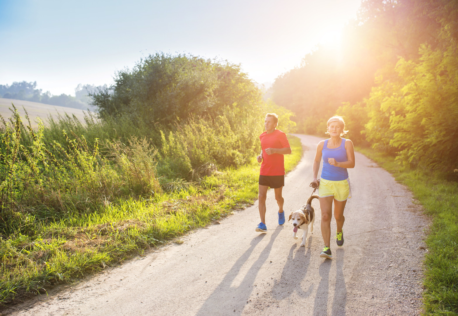 Male and female runners jogging on a paved trail with a small dog