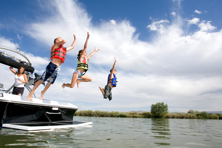 Multiple kids wearing lifejackets and playfully jumping into a lake off the back of a boat