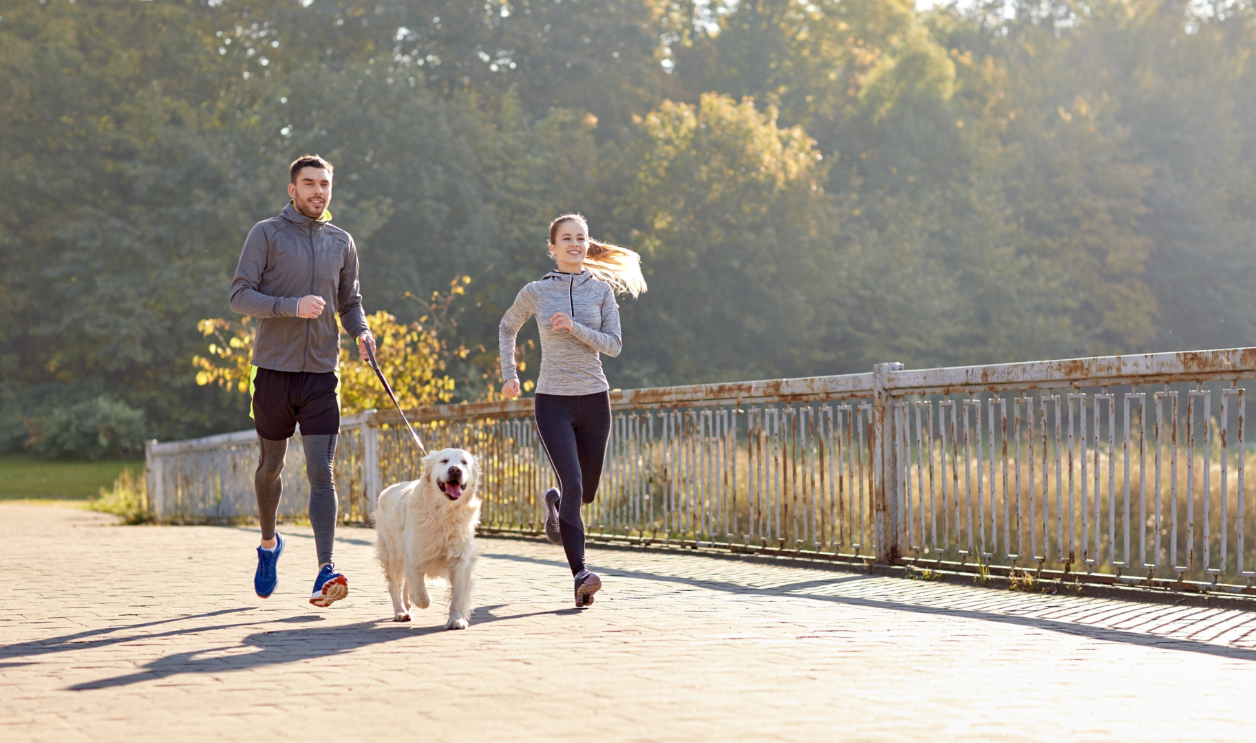 happy couple with dog running outdoors redbud physical thera