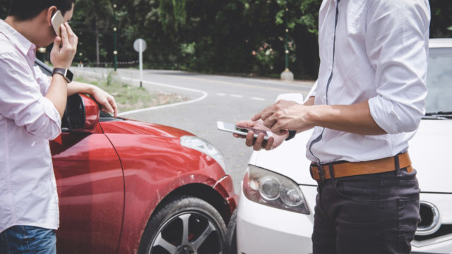 Two drivers man arguing after a car traffic accident collision and making phone call to Insurance Agent, Traffic Accident and insurance concept.
